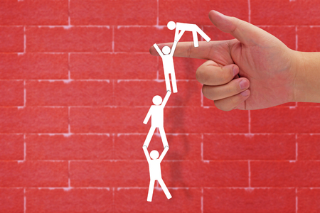 Business teamwork concept, paper cut people climbing on red brick wall background, group of people helping each other Stock Photo