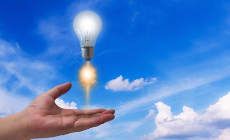 Business idea concept, light bulb rocket launch on blue sky background