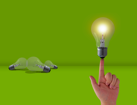 Think different concept, hand and light bulb on green background Stock Photo
