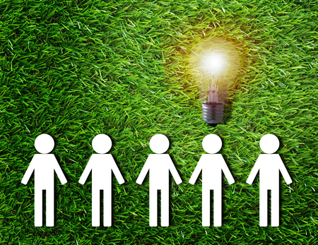 Think different concept, group of white paper people and light bulb on green grass background Stock Photo