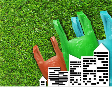 Pollution problem concept, plastic bag and city on green grass background