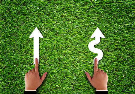 Business alignment concept, strategy and planning, hand and arrow on green grass background