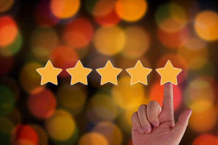 Rating and evaluation concept.  hand and five yellow star on blur background