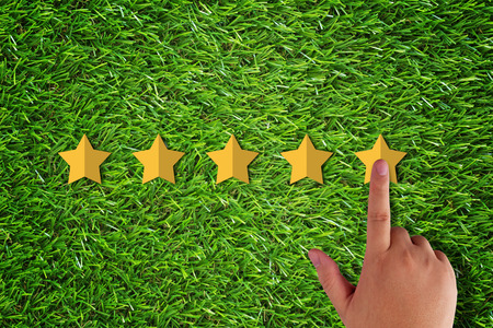 Rating and evaluation concept.  hand and five yellow star on green grass background