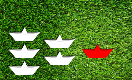 advice: Leadership concept, paper boat on green grass background, business success concept