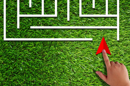 Business challenge, finding solution, resolve problem concept, hand holding red arrow and maze on green grass background Stock Photo