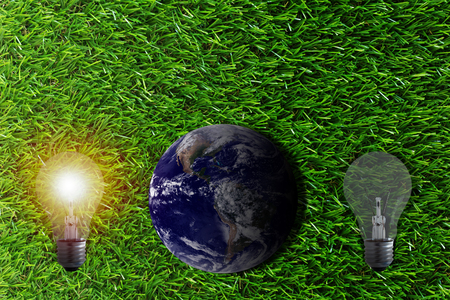 conservative: Ecology concept, save energy, the earth and light bulb on green grass background, Elements of this image furnished by NASA