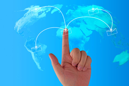 Email concept, world map and hand on blue background, Elements of this image furnished by NASA
