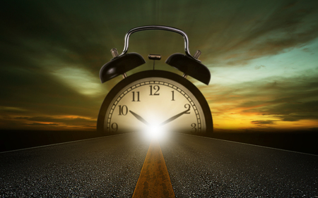 Time management concept, road and alarm clock on sky background Imagens