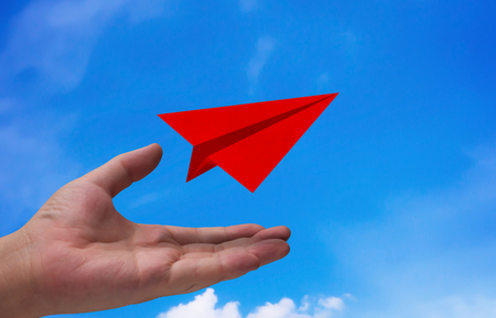Business start concept, strategy and planning, road to success, hand and red airplane paper on blue sky background