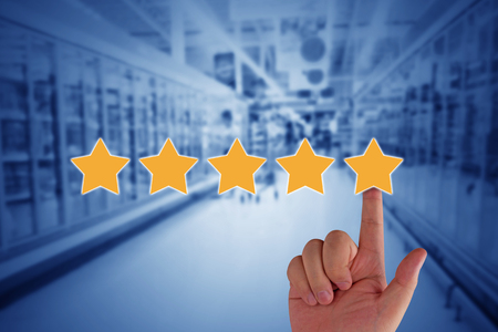 Customer experience concept, service rating on blue background, hand and yellow star Foto de archivo