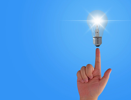 Idea concept, light bulb and hand on blue background
