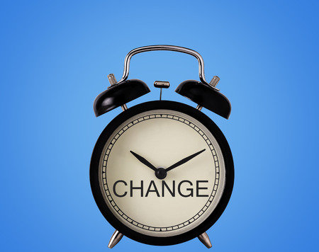 Business time to change concept, alarm clock on blue background