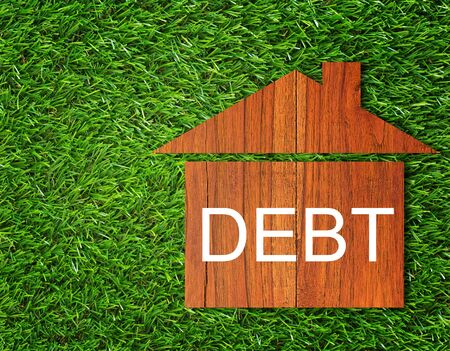 Debt concept, financial crisis, money problem, home loan on green grass background