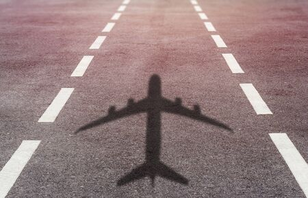 Travel concept, airplane shadow on runway