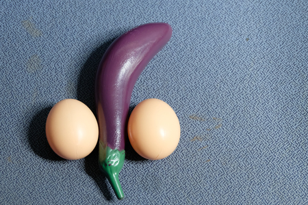 Eggplant and eggs are placed on a blue background. Looks like a penis symbol. Reklamní fotografie - 96620822