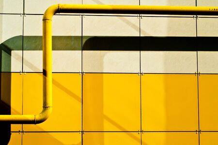 gas pipe: Yellow gas pipe on the background of the wall
