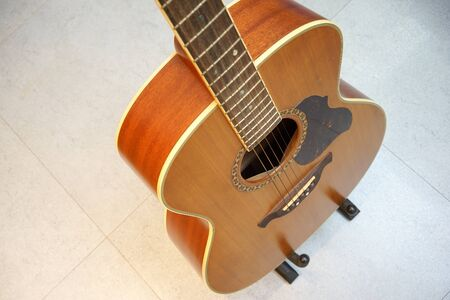 high angle view: Acoustic guitar in high angle view with grey tiles background Stock Photo