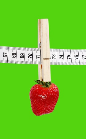 One strawberry hanging on the measuring tape with clothespin isolated on a green surface. photo