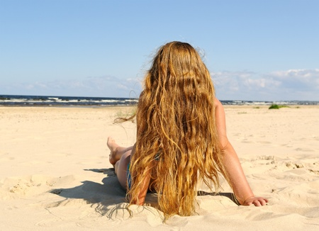 Young girl with long hair is sitting on a sand at the Baltic sea.