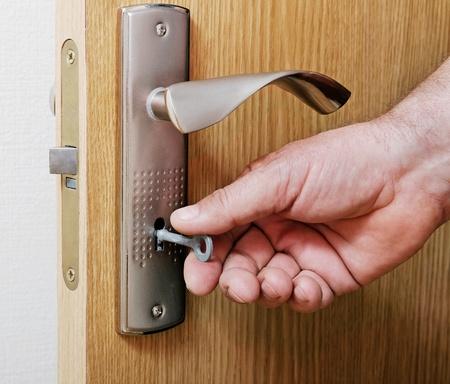 Man put key in the keyhole. Stock Photo - 10747589