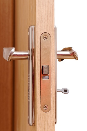 Open door with key on the white surface. Stock Photo