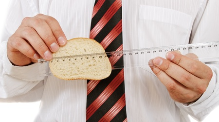 Man measured slice of white bread by ruler. photo