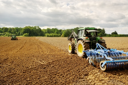 Two tractors working on the plowed land. photo