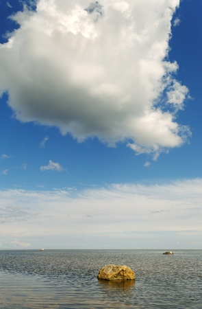 Big stone into Baltic sea and white cloud. photo