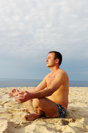 Young man is meditation at the sea. photo