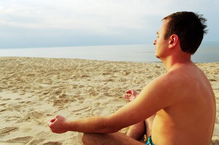 Young man is meditation on the beach at the sea. photo