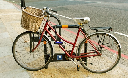Old bicycle on a side walk with bag. photo