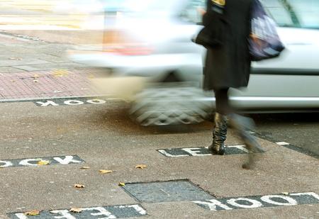 Woman is going across the London street, photo has defocus elements. photo