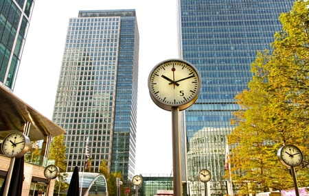 Downtown in the London with clocks and skyscrapers. Editorial