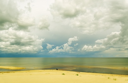 Man sitting at the Baltic sea in a cloudy day. Stock Photo