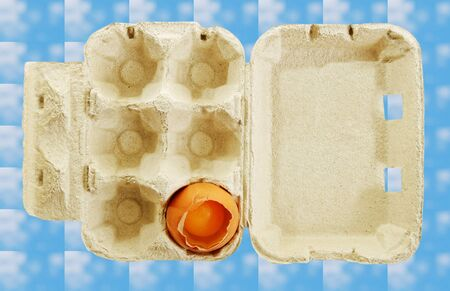 One broken egg in a box, isolated on blue surface. photo