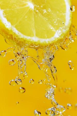 Fresh slice of lemon and water splash on an orange surface  Banque d'images