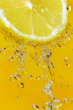 Fresh slice of lemon and water splash on an orange surface  Stockfoto