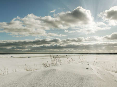 Sun above snowy sea beach  Stock Photo
