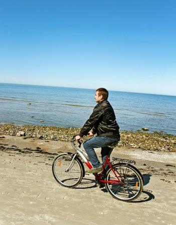 Man with bike on the beach  photo