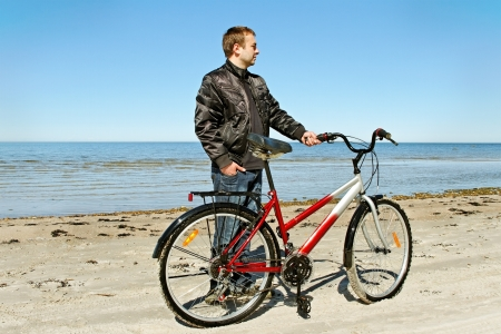 Man with bike on beach of the Baltic sea  photo