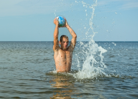 Man play with ball in the water  photo