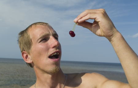 Young man eating the cherry on the beach, unhealthy teeth  photo