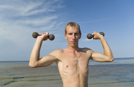 Young man exercise with dumbbells on the beach  photo