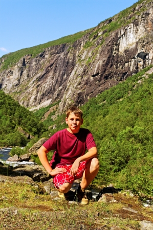 Boy is sitting on a stone at the Voringsfossen waterfall in Norway   photo