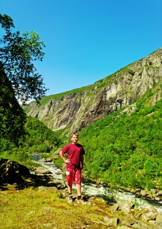 Boy  on a stone at the Voringsfossen waterfall in Norway  photo