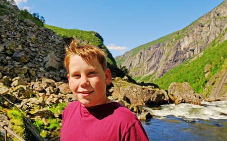 Boy on the cable bridge above mountain river  photo