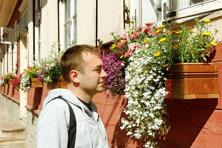 Young man at the flower box on street of old town  photo