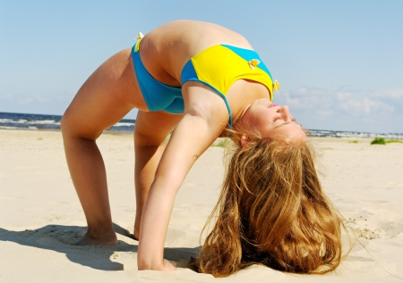 Girl exercise on a sand at the Baltic sea beach  photo