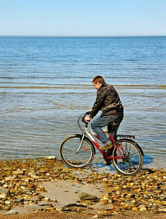 Young man is bicycling at the sea  photo